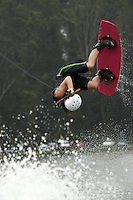 A female wakeboard competitor flips upside down during her tricks run during a competition.