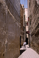 """Fez, Morocco - Narrow Street with """"Harem Windows"""" protruding from the second story.  In earlier times when women were secluded, the slots in these """"windows"""" allowed them to view activities in the street below without being seen."""
