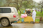 A man purchases some cotton candy in the rainy valley of Wadi Darbat, Oman. During the monsoon season thousands of people from across the Arabian Peninsula come to the rainy region of Southern Oman to escape the heat.