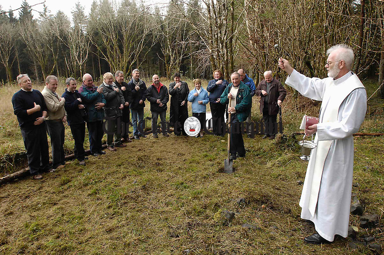Fr Pat O Neill, PP Ruan, blesses the site for the new 250 Cancer Centre at Ballygriffey Ruan, flanked by Tom O Grady who cut the first sod and watched by members of the Clare 250 Cycle including John Dunne. Photograph by John Kelly.