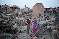 Two women stand on their destroyed house in the ancient city of Bhaktapur, in the Kathmandu Valley, Nepal. May 1, 2015