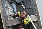 """A young girl in Ganvie sits in a boat, looking up at the camera.  Ganvie, Benin, with some 3,000 stilted buildings and a population of 20,000-30,000 people, may be the largest """"lake vllage"""" in Africa.  In Ganvie, the population lives exclusively from fishing, building houses on stilts in and next to Lake Nokoue.  Because the Dan-Homey religion prohibited attacks on communities living in the water, the village of Ganvie dates back to the 16th or 17th century, when it was built to protect people from slavery.  Even Ganvie's fruit and vegetable market is on water!!!"""