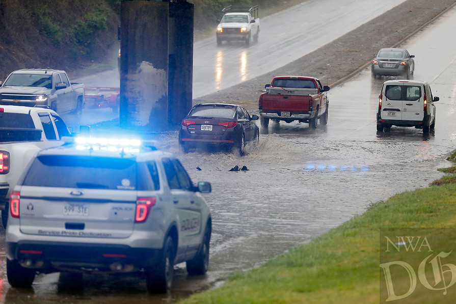 The Springdale Police Department monitors traffic and a stalled vehicle Wednesday, April 28, 2021, morning approaching a secant of the Arkansas and Missouri Railroad tracks on So. Thompson Street in Springdale. The National Weather Service office in Tulsa said the storm system that began moving through Northwest Arkansas Tuesday night had dropped from 1 to 3 inches of rain across the area by mid-morning Wednesday. With rainfall of 4 to 6 inches being reported in some areas. Check out nwaonline.com/210429Daily/ and nwadg.com/photos for a photo gallery.<br /> (NWA Democrat-Gazette/David Gottschalk)
