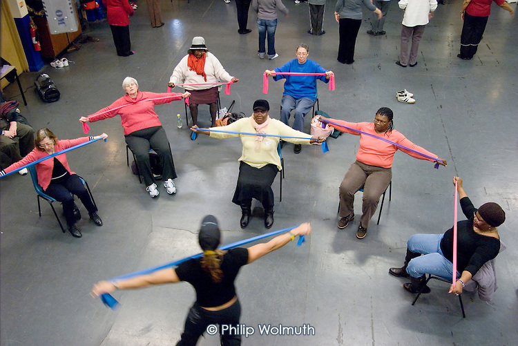 Chair-based exercise session at Open Age open day at Paddington Arts (ballet class in background)