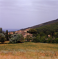 The medieval village with its terracotta tiled roofs seen from across the fields