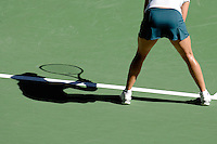 A shadow of a woman playing tennis on a court.