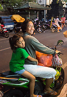 Bali, Indonesia.  Mother and daughter Going Home after Early-morning Shopping in the Jimbaran Market.