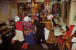 Mount Zion Baptist Church north London. Members of the congreation hold hands kneeling around a spiritual prayer pole in the main room of their church.  from A STORM IS PASSING OVER a Look at Black Churches in Britain. Published by Thames and Hudson isbn 0 500 27826 1 1990s