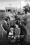"""Gypsy family camped at roadside,  casual seasonal fruit picking Wisbech Cambridgeshire Uk 1977.<br /> <br /> Mr Jessie Holland Davis with six of his ten children. (Front to back) Alan, Billy, Frank in front of the fire looking into the camera, with Musher (Jessie) Davis behind. Teen girl to left with arms crossed is Shirley. Sheila Anne to right behind Musher. And at the back, is Annie Smith who is married to Musher and is a Davis. Missing from the pictures are Rita, an elder daughter, Albert known as Mousey, Leonard and baby John, who would have been in the trailer with their mother Doreen Davis. The Davis family  are (in 2016) """"mostly settled travellers now"""", still living in East Anglia.<br /> <br /> Caption details thanks to Frank Davis."""