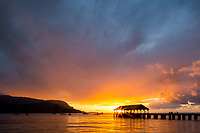 Sunbursts are seen through the structure at the end of Hanalei Pier, which is silhouetted by a brilliant summer sunset at Hanalei Bay, Kaua'i.
