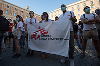 """NGO: Medici Senza Frontiere (Médecins sans frontières, Doctors Without Borders).<br /> <br /> Rome, 27/07/2020. Today, hundreds of people, NGO's (ONG) representatives, actors and politicians gathered in Piazza San Silvestro (near the Italian Parliament) to protest (1.) against the dramatic situation in Libya - erupted in a civil war between the GNA (2.) and the forces of General Khalifa Belqasim Haftar - and to protest against the inhumane conditions of migrant people trapped in legal and illegal prisons in Libya. The aim of the demo was to call the Italian Government to stop funding the """"Libyan Coast Guard"""" and to immediately help and free People in Libya throughout """"Humanitarian Corridors"""", and give them the protection they are entitled of by the International Human Rights Conventions. <br /> From the organisers Facebook event page: «[…] we meet to ask the Italian Government and the European States to stop funding the so-called Libyan coast guard, to close and evacuate the detention centres by transferring migrants out of Libya and to promote corridors to help people on the run find protection without endangering their lives. The men, women and children who take the sea from the Libyan coast flee from situations of extreme misery, despotic regimes, tribal persecutions, ethnic conflicts, wars and environmental catastrophes. And in Libya they are subjected to violence, extortion, detention, torture, rape and torture. A few days ago, on July 16, the Chamber of Deputies [Of the Italian Parliament, ndr] for the fourth consecutive year approved the financing of the Italian mission in Libya, which provides financial support for the so-called Libyan coastguard and training and training of its members. […] The mobilization will be accompanied by readings by Ascanio Celestini, Valentina Carnelutti, Fabrizio Gifuni and Sonia Bergamasco […]».<br /> <br /> Footnotes & Links:<br /> 1. http://bit.do/fG3Eu<br /> 2. 07.05.19 Prime Minister of Libya Fayez al-Serraj Met Italian PM G"""