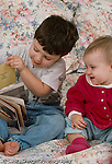 15 month old baby girl sitting with 3 year old brother looking at book he holds interested language development vertical Caucasian