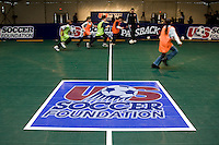 A group of local children run across the pitch provided by Sport Court during a US Soccer Foundation clinic held at City Center in Washington, DC.