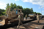 "American soldiers with the 15th Engineer Battalion help unload $28.5 million of equipment including (at left) a D7 Romeo and (at right) a light equipment transporter for a two week-long NATO exercise at the Drawsko Pomorskie Training Area in Poland on June 10, 2015.  NATO is engaged in a multilateral training exercise ""Saber Strike,"" the first time Poland has hosted such war games, involving the militaries of Canada, Denmark, Germany, Poland, and the United States."