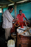 Two Melanesian men pumping out gasoline from a barrel at a service station, Vanuatu.
