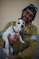 Firefighter of Brica's Malaga 703 of the service of Andalucian Infoca Plan, Francisco Perez and his dog Lola pose for the photographer after finish work in the wildfire in El Ronquillo, near Sevilla on July 26, 2015.<br /> Since July 19 wildfires have ravaged nearly 39,000 hectares of land in Spain, according to the provisional figures from the agriculture ministry. © Pedro ARMESTRE