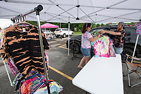 Michael Berndt (right) and Shanna Perry, both of Prairie Grove, get their tie-dye shirts ready to sell Sunday June 6, 2021 at the Farmington Farmers Market at the Farmington Junior High School parking lot. The market is held each Sunday from 9 A.M. to 2 P.M. from May through October. For information about the market see www.busybeescanningco.com/markets  Visit nwaonline.com/2100607Daily/ and nwadg.com/photo. (NWA Democrat-Gazette/J.T. Wampler)
