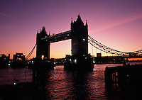 The Tower Bridge in silhouette over the River Thames at sunset. London, England.