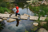 Young boy in red shirt walks across a rock bridge over a small pond in park with clouds reflected in water