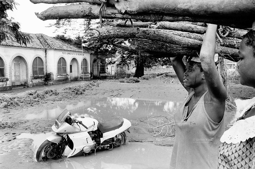 Mozambique. Province of Gaza. Barragem. The Limpopo river has flooded the whole town. The post office is surrounded with water. A motorbike Suzuki is stuck in the mud. Two women carry wood on their heads.© 2000 Didier Ruef