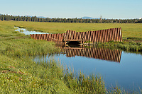 Irrigation culvert/canal flowing from small reservoir, Timmerman Ranch, Williamson River, Oregon.  June.