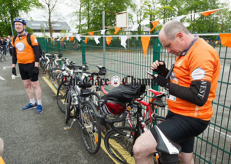 Cyclist Brendan O Shea checks his phone as the Cycle Against Suicide arrives to Colaiste Muire, Ennis. Photograph by John Kelly.