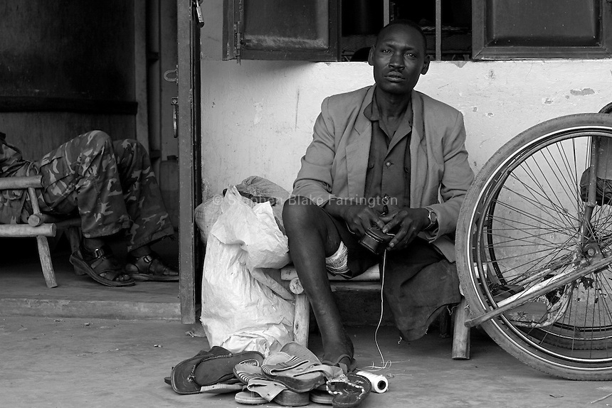 David, pictured here, was maimed by a land mine in 1995. He now repairs shoes near the Unyama Internally Displaced PeopleÕs (IDPs) camp. The war in Northern Uganda began in 1986 between the LordÕs Resistance Army (LRA) and the Ugandan PeopleÕs Defense Forces (UPDF). The LRA has reigned terror and carnage on Northern Uganda and Southern Sudan ever since. The rebels commonly abduct children to fuel their personnel needs and quickly turn them into soldiers, porters and sexual slaves. The ongoing war has significantly damaged the region and has left an ongoing burden on the local population. Unyama (off Kitgum Road North) Gulu District, Uganda, Africa. December 2005 © Stephen Blake Farrington