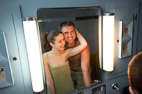 Reflection of young couple smiling in bathroom mirror