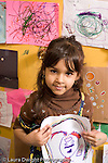 Educaton preschool  3-4 year olds art activity emotion pride girl holding up her drawing made with markers recognizable shapes vertical