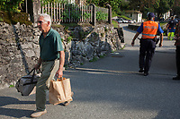 Switzerland. Canton Graubunden. Bregaglia valley. Bondo. A man who had returned to his home had to be evacuated from the village for the second time due to a second massive landslide while the remote village was still recovering from a huge landslide caused by a giant rockslide swept down from Piz Cengalo on August 23, 2017. The man carries a travelling bag and a paper bag with his small belongings. A police officer is on duty to prohibit people to enter the village and to ensure safety. 25.08.2017 © 2017 Didier Ruef