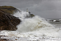 Waves crash against rocks by the lighthouse in Mumbles, caused by 70mph gusts  near Swansea, Wales, UK. Friday 21 May 2021