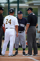 GCL Yankees manager Marc Bombard lineup exchange with Milver Reyes (24) as umpires Zach Neff (left) and Conner Colhane (right) look on during the second game of a doubleheader against the GCL Pirates on July 31, 2015 at the Pirate City in Bradenton, Florida.  The game was suspended after two innings due to rain.  (Mike Janes/Four Seam Images)