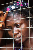 Nigeria. Enugu State. Agbani. Igbo funeral ceremony of Mrs Ann Mary Azuka Nbubuisi Anike who passed away at 72 years old. One her daughters looks with sadness though a window with bars at her mother's burial in the family home's garden. The woman wears a head tie which is a women's cloth head scarf. The head tie is used as an ornamental head covering or fashion accessory, or for functionality in different settings. Its use or meaning can vary depending on the country and/or religion of those who wear it. The head tie is called gele in Nigeria. 11.07.19 © 2019 Didier Ruef