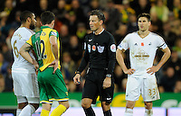 Referee Mark Clattenburg talks to Ashley Williams of Swansea City and Robbie Brady of Norwich City during the Barclays Premier League match between Norwich City and Swansea City played at Carrow Road, Norwich on November 7th 2015