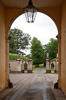 View through an archway under Badminton House clock tower towards the gateway out into the estate