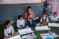 Nepal, Kathmandu. Clark Memorial School. Counselor from Ankur counseling and training helping children and their teachers deal with ongoing trauma from the earthquake. Children expressing themselves through painting.