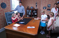 """Former Congressman and Fox News host John Kasich and his family play at his desk before he signed copies of his new book, """"Stand for Something"""", in the Westerville Public Library reproduction of his Washington office. The library opened Sunday, June 11, 2006, the offices containing Kasich's historical records and personal library from his years as a U.S. congressman.<br />"""