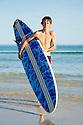 Teenage boy at beach holding a surfboard.