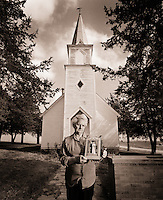 A senior woman poses outside of a church holding a wedding picture. She has a sorowful expression.