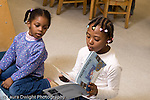 Preschool 4-5 year olds girl looking over at picture book her friend is looking at horizontal