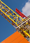 Yellow Tower Crane - Yellow tower crane, red concreete pump, orange building, blue sky