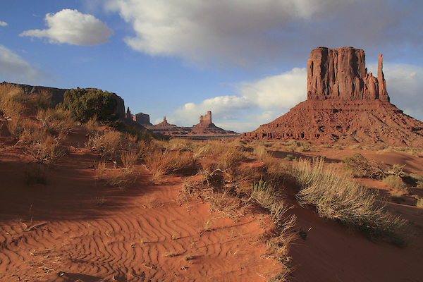 The Mittens rock formation and sand dunes in Monument Valley Navajo Tribal Park, Arizona, USA. . John offers private photo tours in Monument Valley and throughout Arizona, Utah and Colorado. Year-round.