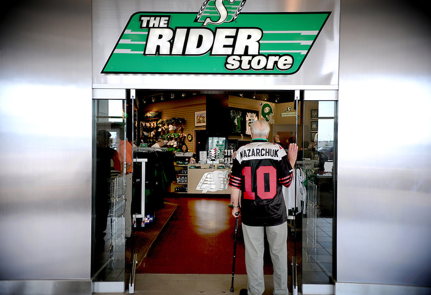 Peter Nazarchuk, a right tackle for the Saskatchewan Roughriders in 1942 and 1943, peaks into The Rider Store in Regina while wearing a retro jersey the team unveiled in 2010 to mark the team's 100th season. THE CANADIAN PRESS/Mark Taylor.