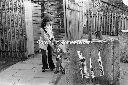 Derry Northern Ireland Londonderry. 1979. Young mother Colette Jones and son Fred Jones at Butchers Gate. The torn poster is for Bernadette Devlin, who ran for the Irish Republican Socialist Party in the 1979 elections to the European Parliament in the Northern Ireland constituency, and won 5.9% of the vote.