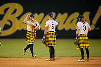 Savannah Bananas outfielder Bill Knight (4) high fives Gabe Howell (6) and Kyler Marquis (3) after closing out a Coastal Plain League game against the Macon Bacon on July 15, 2020 at Grayson Stadium in Savannah, Georgia.  Savannah wore kilts for their St. Patrick's Day in July promotion.  (Mike Janes/Four Seam Images)