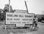 Harrisonville PA:  View of Brady Stewart Jr. standing next to the famous Sideling Hill Summit sign on Route 30 in Fulton County.