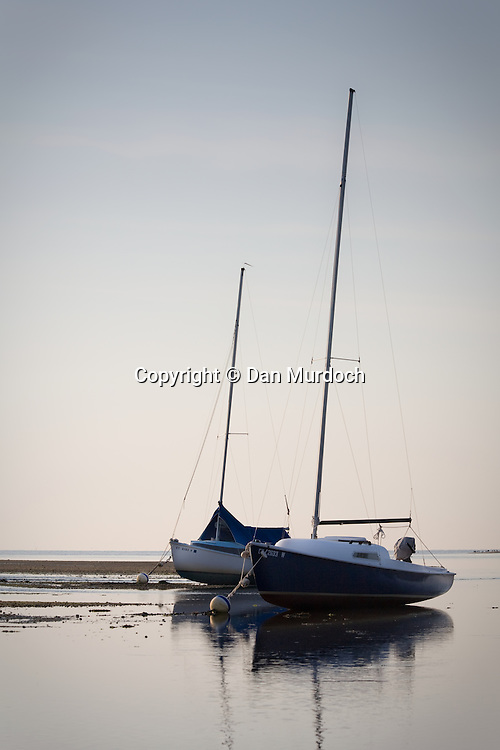 two sailboats aground at low tide