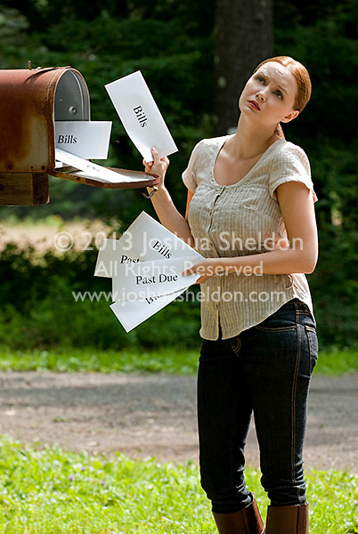 Young woman receiving bills in her mailbox