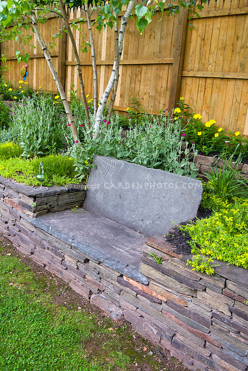 Built in stone bench in stone wall raised bed garden