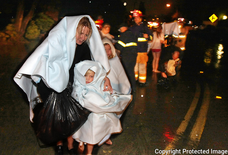 Lisa Dupre is blanketed with the two children she cares for after being rescued from their flooded car in Solana Beach, California which was stranded after a severe rainstorm in January, 2010.    photo for the North County Times